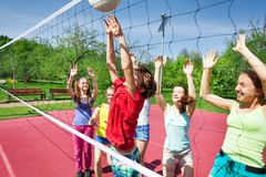 Anni dell'adolescenza felici con le armi su pallavolo del gioco vicino a rete Fotografie Stock Libere da Diritti