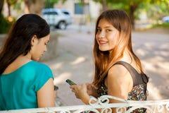 Anni dell'adolescenza felici con un telefono cellulare Fotografia Stock Libera da Diritti
