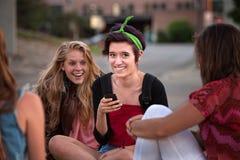 Anni dell'adolescenza femminili emozionanti che esaminano telefono Fotografie Stock