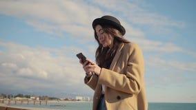 Anni dell'adolescenza moderni con il cellulare su una riva stock footage