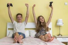 Anni dell'adolescenza ragazzo e ragazza che giocano la console del gioco Immagini Stock Libere da Diritti