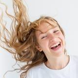 Anni dell'adolescenza sorridenti della ragazza del ritratto con i capelli ricci di volo fotografia stock libera da diritti