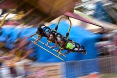 Anni dell'adolescenza su una sfuocatura di movimento di giro di carnevale di volo Fotografie Stock