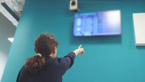 Anni dell'adolescenza turistici della ragazza che guardano il programma di volo della sua partenza l'aeroporto esaminando il bord video d archivio