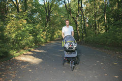30 anni dell'uomo con un passeggiatore che cammina nel Immagine Stock Libera da Diritti