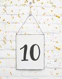 10 anni della carta della festa di compleanno con il numero dieci con il raggiro dorato Immagine Stock