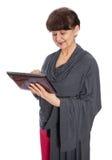 65 anni della donna che cerca in Internet, Londra Fotografia Stock
