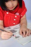 3 anni della ragazza asiatica disegna e sketchs molti visi umani con la p Fotografia Stock