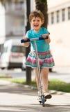 4 anni della ragazza che resta con il motorino Fotografia Stock