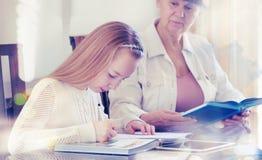10 anni della ragazza ed il suo insegnante Studio della bambina durante la sua lezione privata Concetto d'istruzione ed educativo Fotografie Stock