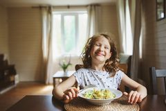 8 anni della ragazza felice del bambino che mangia pasta a casa Immagini Stock