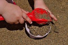 3 anni della ragazza passa mettere la sabbia nella forma pattypan rosa con la pala rossa Immagini Stock Libere da Diritti