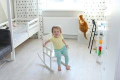 2 anni di bambina nella sua stanza che si siede su una sedia di oscillazione Immagini Stock