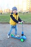 3 anni di bambino con il motorino all'aperto nella primavera Fotografia Stock