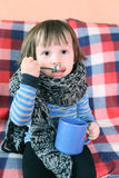2 anni di bambino malato in sciarpa e tazza di lana calde di tè a casa Immagine Stock