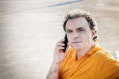 40 anni di classe dello sportivo che parla su un telefono cellulare Fotografie Stock