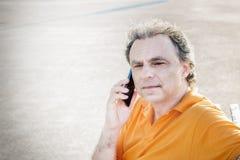 40 anni di classe dello sportivo che parla su un telefono cellulare Immagini Stock