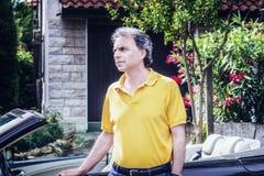40 anni di classe dello sportivo che si siede sulla porta di automobile del cabriolet Immagini Stock