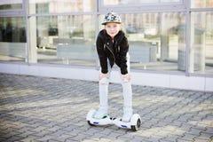 10 anni di guida della ragazza sull'auto che equilibra pattino elettrico Fotografia Stock Libera da Diritti