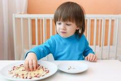 2 anni di ragazzino adorabile gioca con riso ed i fagioli di coperture Fotografia Stock