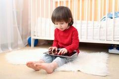 2 anni di ragazzo in camicia rossa con il computer della compressa Fotografia Stock