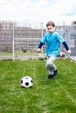 7 anni di ragazzo che dà dei calci alla palla nel giardino Immagini Stock