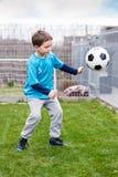 7 anni di ragazzo che dà dei calci alla palla nel giardino Fotografia Stock