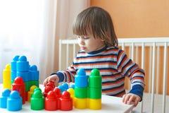 2 anni di ragazzo del bambino che gioca i blocchi di plastica a casa Fotografia Stock Libera da Diritti