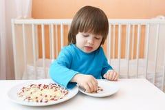 2 anni di ragazzo gioca con riso ed i fagioli di coperture Fotografia Stock Libera da Diritti