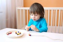 2 anni di ragazzo hanno fatto le perle Immagini Stock Libere da Diritti