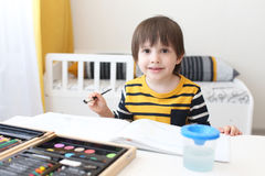 3 anni di ragazzo sta dipingendo con l'acquerello Fotografia Stock