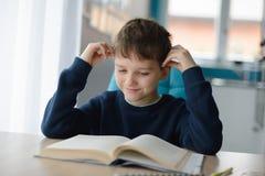 8 anni felici del ragazzo che fa il suo compito alla tavola Fotografie Stock Libere da Diritti
