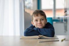 8 anni felici del ragazzo che fa il suo compito alla tavola Immagini Stock Libere da Diritti