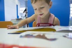 2 anni felici del ragazzo di storie di lettura rapida alla biblioteca Fotografia Stock Libera da Diritti