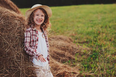 7 anni felici della ragazza del bambino in camicia e cappello di plaid stile country che si rilassano sul campo di estate con le  Fotografie Stock