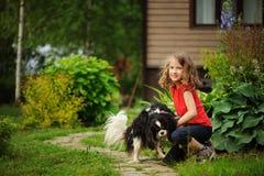 8 anni felici della ragazza del bambino che gioca con il suo cane dello spaniel Fotografie Stock Libere da Diritti
