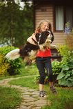 8 anni felici della ragazza del bambino che gioca con il suo cane dello spaniel all'aperto Immagine Stock Libera da Diritti