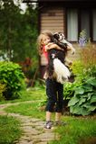 8 anni felici della ragazza del bambino che gioca con il suo cane dello spaniel all'aperto Immagini Stock Libere da Diritti