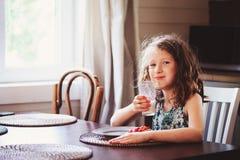 8 anni felici della ragazza del bambino che mangia prima colazione nel kitche del paese Fotografie Stock Libere da Diritti