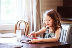 8 anni felici della ragazza del bambino che mangia prima colazione nella cucina del paese Fotografie Stock Libere da Diritti