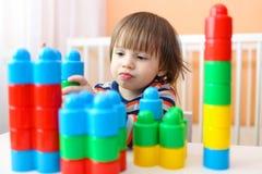 2 anni felici di bambino che gioca i blocchi di plastica Fotografie Stock Libere da Diritti