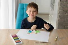8 anni felici di bambino del ragazzo che estrae una cartolina d'auguri per sua nonna Fotografie Stock Libere da Diritti