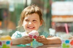3 anni felici di ragazza che mangia il gelato Immagine Stock