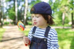2 anni felici di ragazzo con il lecca lecca all'aperto di estate Fotografia Stock