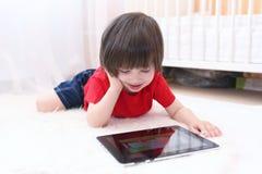 2 anni felici di ragazzo in maglietta rossa con il computer della compressa Immagine Stock