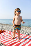 2 anni felici di ragazzo in occhiali da sole sulla spiaggia di pietra Immagini Stock