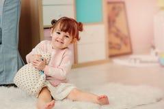 2 anni felici svegli della neonata che gioca con i giocattoli a casa Fotografia Stock