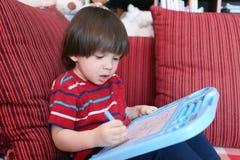 2 anni piacevoli di pittura del bambino sulla compressa magnetica Fotografie Stock Libere da Diritti