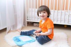 2 anni piacevoli di pittura del bambino sulla compressa magnetica a casa Immagini Stock Libere da Diritti