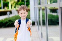7 anni piccoli felici di scolaro che mostra i pollici su Fotografia Stock